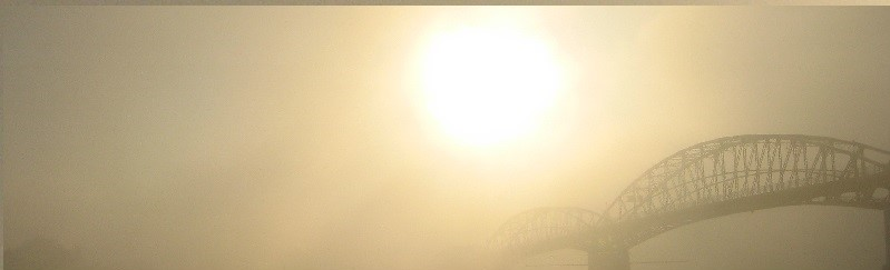 Sun emerging from fog, showing detail of half-hidden structure